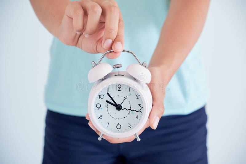 Sluit omhoog van een zieke jonge vrouw met een klok in haar handen het concept regelgeving van de menstruele cyclus tijd om h te  stock afbeelding