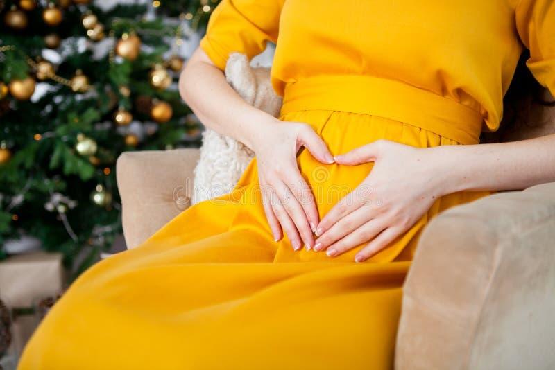 Sluit omhoog van een zwangere vrouw die een hart op haar buik op maken royalty-vrije stock fotografie