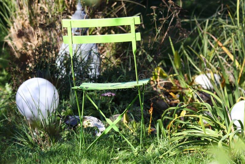 Sluit omhoog van eenzame geïsoleerde groene houten vouwende stoel in de tuin met grassen, groen riet, elektrische ronde lampen royalty-vrije stock foto