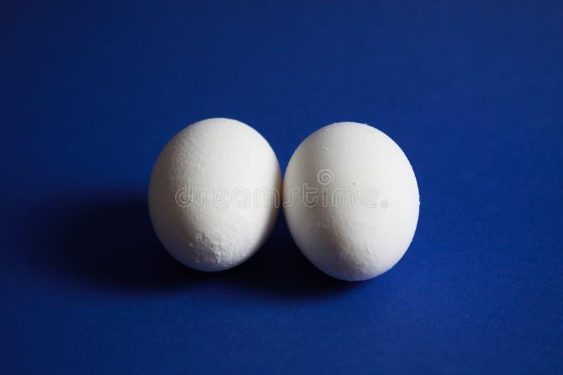Sluit omhoog van geïsoleerd twee eieren met blauwe achtergrond stock afbeeldingen