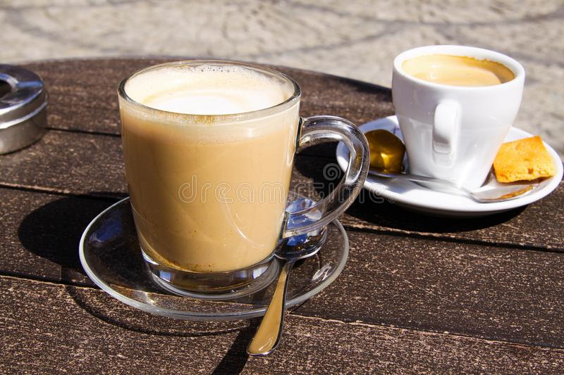 Sluit omhoog van geïsoleerde bruine Nederlandse melkkoffie koffie verkeerd in transparante glasmok en witte espressokop stock foto's