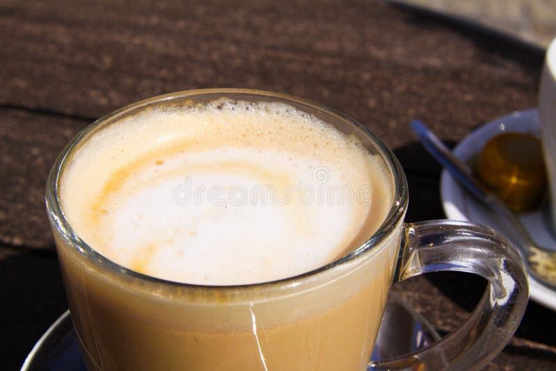 Sluit omhoog van geïsoleerde bruine Nederlandse melkkoffie koffie verkeerd in transparante glasmok royalty-vrije stock foto