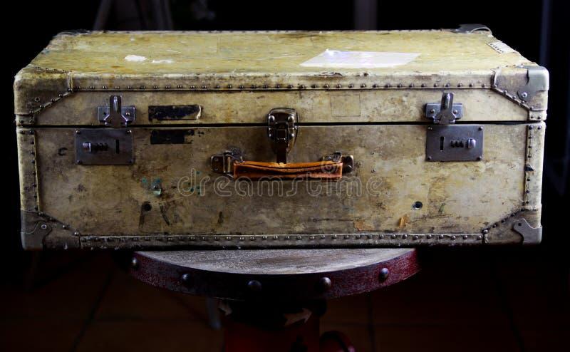 Sluit omhoog van geïsoleerde oude gebruikte koffer met klinknagels, leergreep en combinatiesloten royalty-vrije stock foto's