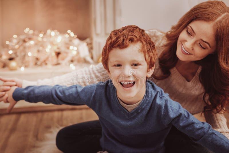 Sluit omhoog van geamuseerde kindzitting met zijn moeder stock afbeelding
