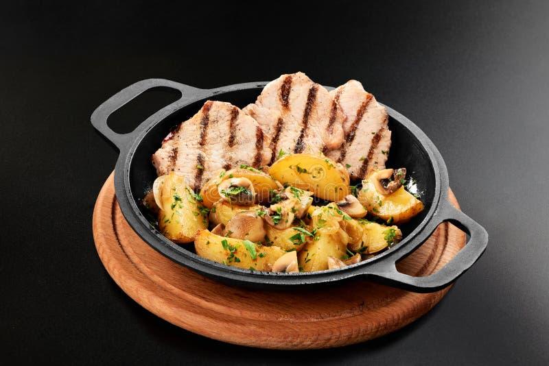 Sluit omhoog van gebraden aardappels met de borst van de paddestoelkip in pan bij de zwarte grill van het achtergrondmenurestaura royalty-vrije stock afbeeldingen