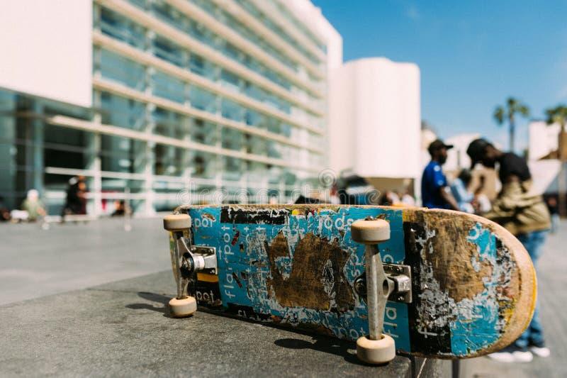 Sluit omhoog van gebruikt skateboard in stedelijk milieu tijdens zonnige dag met duidelijke blauwe hemel op muur stock foto's