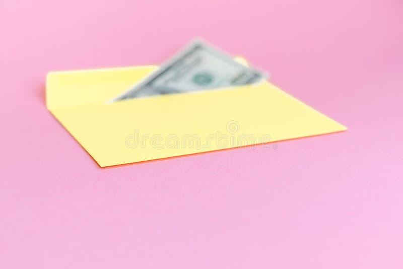 Sluit omhoog van geld in gele envelop liggen op de pastelkleur roze achtergrond Het brandmerken spot omhoog; vooraanzicht stock afbeeldingen