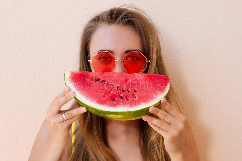 Sluit omhoog van Gelukkig Meisje in roze zonnebril en watermeloenfruit De zomervakantie en het weekend van de prettijd Zomerconce stock foto