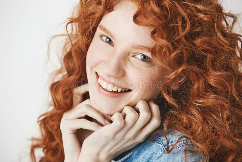 Sluit omhoog van gelukkig mooi meisje met het krullende gemberhaar glimlachen bekijkend camera Witte achtergrond royalty-vrije stock afbeelding