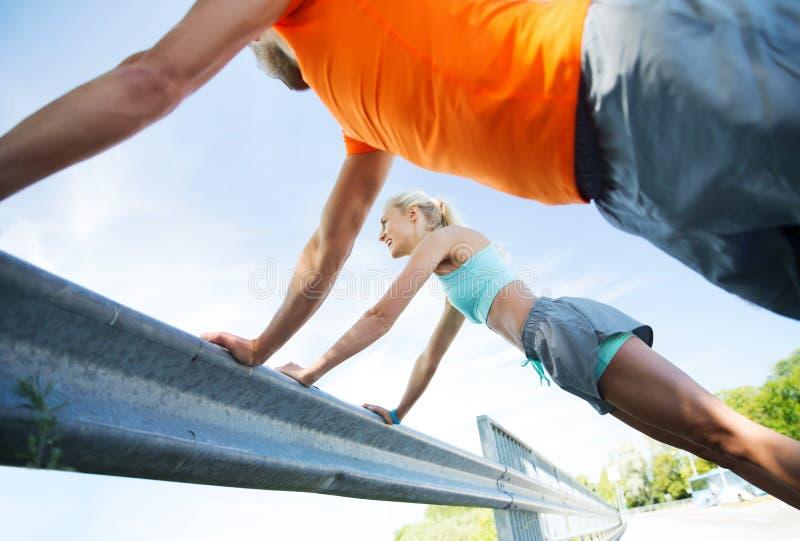 Sluit omhoog van gelukkig paar die opdrukoefeningen in openlucht doen royalty-vrije stock afbeelding