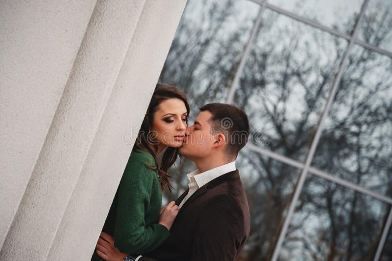 Sluit omhoog van gelukkig romantisch aantrekkelijk jong paar die en bij de straat kussen koesteren royalty-vrije stock afbeeldingen