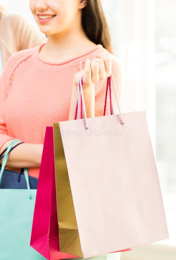 Sluit omhoog van gelukkige tieners met het winkelen zakken stock foto