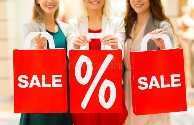 Sluit omhoog van gelukkige vrouwen met het winkelen zakken in wandelgalerij royalty-vrije stock afbeeldingen