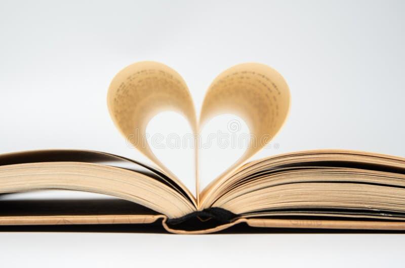 Sluit omhoog van geopend die boek met hart van twee die pagina's wordt gevormd, op witte achtergrond worden geïsoleerd royalty-vrije stock fotografie