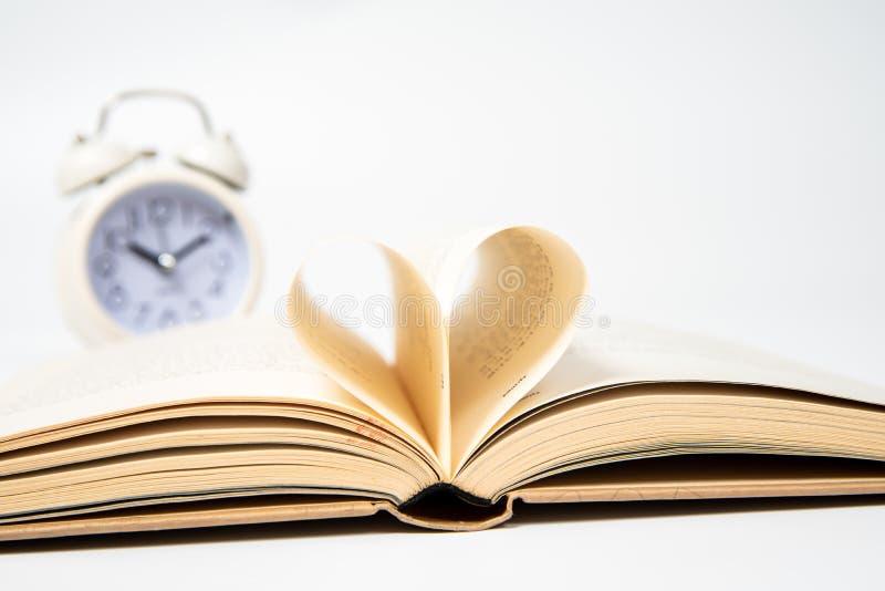 Sluit omhoog van geopend die boek met hart van twee die pagina's wordt gevormd, op witte achtergrond worden geïsoleerd stock fotografie