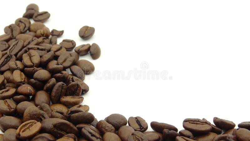 Sluit omhoog van geroosterde koffiebonen op witte achtergrond stock afbeeldingen