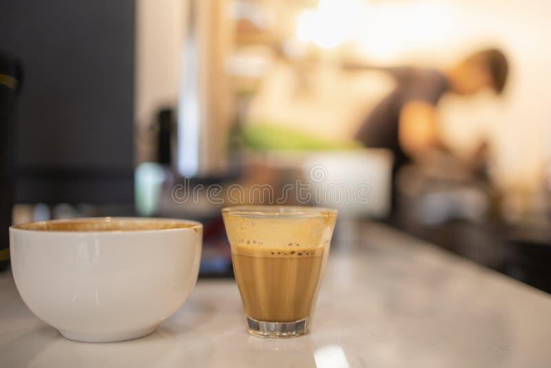 Sluit omhoog van geschoten glas en witte kop van hete koffie latte met koffiezetapparaatmachine en barista als achtergrond stock afbeeldingen