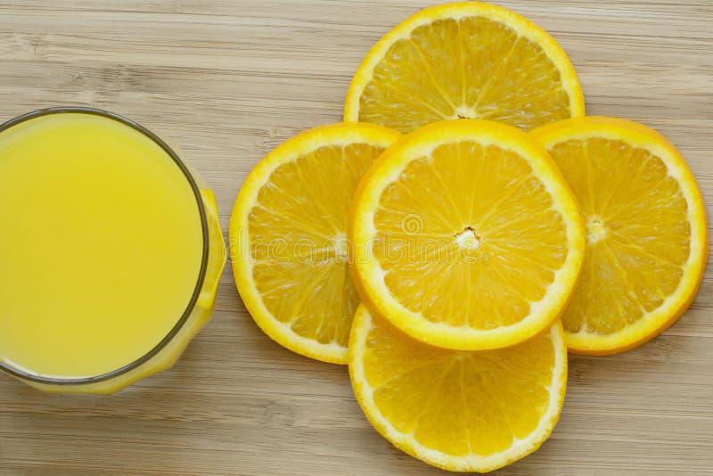 Sluit omhoog van gesneden sinaasappel en een volledig glas jus d'orange op houten oppervlakte stock foto
