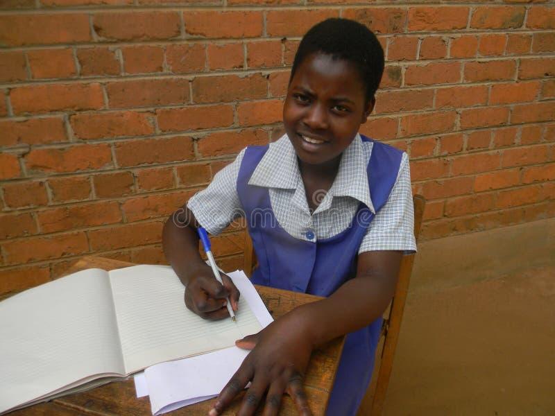 Sluit omhoog van gezet schoolmeisje die in boek schrijven stock foto's