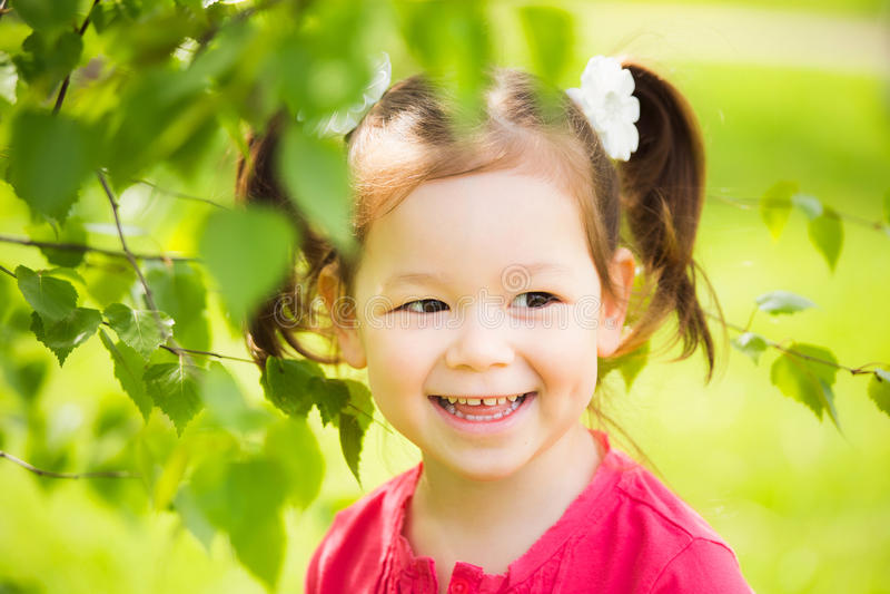 Sluit omhoog van gezicht van kind het spelen huid - en - zoeken in openlucht in park stock foto