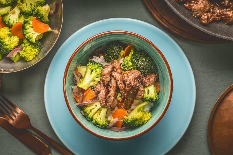 Sluit omhoog van gezonde evenwichtige voedingsmaaltijd in kom met rundvleesvlees, rijst, gestoomde groenten: broccoli en wortelen royalty-vrije stock foto's