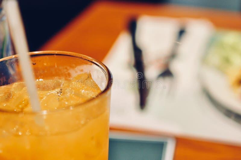 Sluit omhoog van Glas jus d'orange met ijs op de lijst stock afbeeldingen
