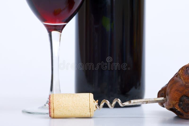 Sluit omhoog van glas van rode wijn, fles en kurketrekker royalty-vrije stock fotografie