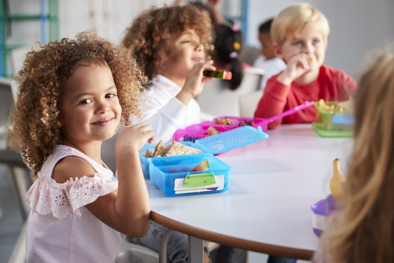 Sluit omhoog van glimlachende jonge kinderen die bij een lijst zitten hun ingepakte lunchen eten samen op zuigelingsschool, meisj stock foto
