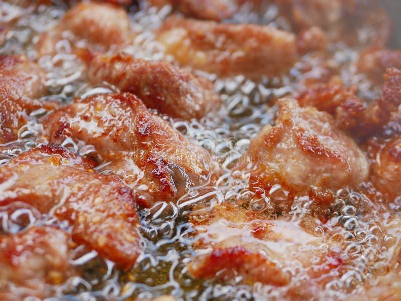 Sluit omhoog van goed uitgevoerd het frituren varkensvlees in kokende/borrelende thuis tafelolie een pan - kok stock foto