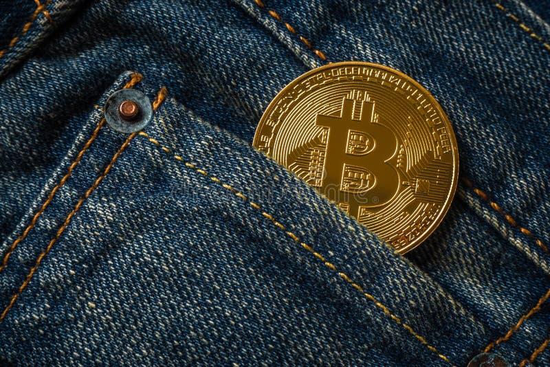 Sluit omhoog van gouden bitcoin in de zak van denimjeans royalty-vrije stock foto's