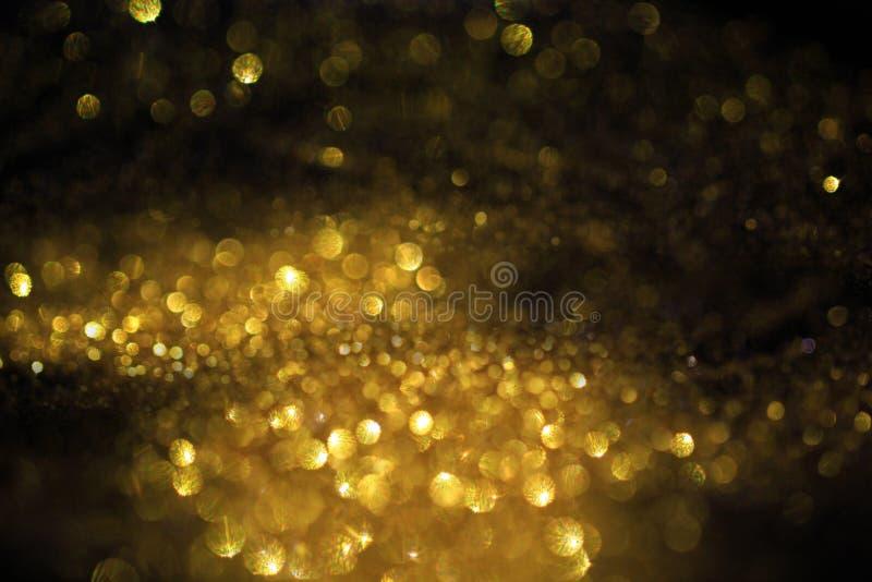 Sluit omhoog van Gouden poeder met schitteren lichten op zwarte achtergrond royalty-vrije stock foto