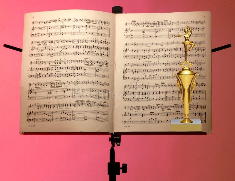 Sluit omhoog van gouden trofee en muzieknotatribune royalty-vrije stock foto's