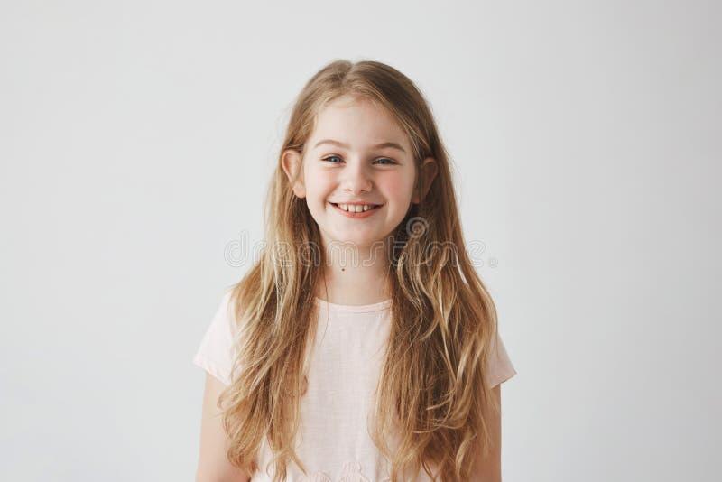 Sluit omhoog van grappig meisje die met blauw ogen en blondehaar, in camera met tevreden uitdrukking kijken lachen stock fotografie