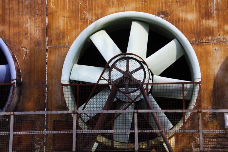 Sluit omhoog van grijze turbine met het drijven van riem en roestige staalmuur royalty-vrije stock fotografie