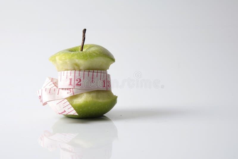 Sluit omhoog van groene die appel met het meten van band op witte achtergrond wordt geïsoleerd royalty-vrije stock afbeeldingen