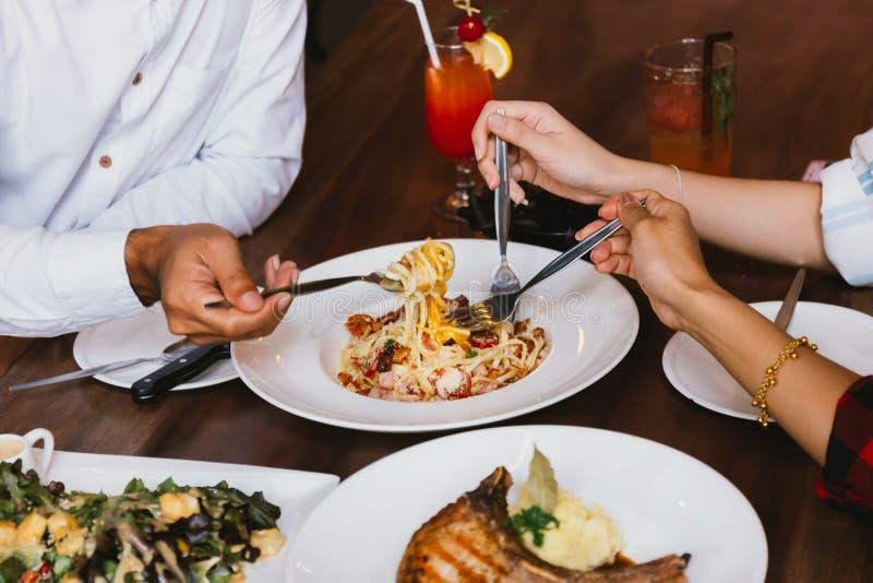 Sluit omhoog van groep vriendenhanden met een vork die pret hebben die en Italiaans diner samen eten hebben royalty-vrije stock fotografie