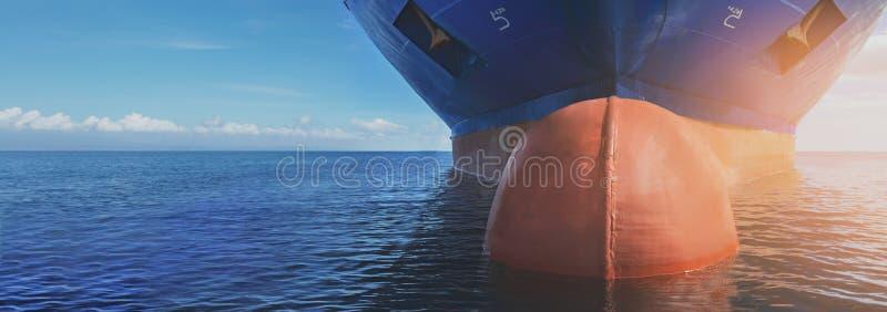 Sluit omhoog van groot blauw koopvaardijcragoschip in het midden van de lopende oceaan Het uitvoeren van van de de ladingsuitvoer royalty-vrije stock afbeeldingen