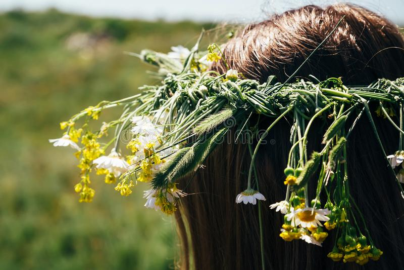 Sluit omhoog van haarkroon van wilde bloemen, jonge vrouw met bloemen in hun haar wordt gemaakt dat royalty-vrije stock foto