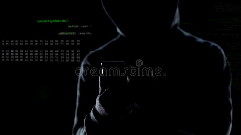 Sluit omhoog van hakker die met een kap cyber aanval op smartphone in werking stellen, lancerend bom stock foto's