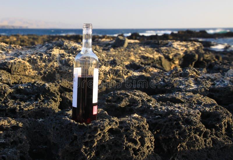 Sluit omhoog van half volledige rode wijnfles op rotsen van strand met oceaangolvenachtergrond - Gr Cotillo, Fuerteventura stock fotografie