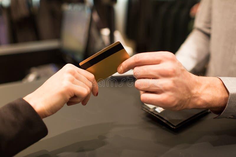 Sluit omhoog van hand die creditcard geven aan verkoper stock afbeeldingen