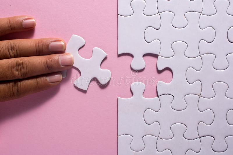 Sluit omhoog van hand plaatsend het laatste puzzelstuk op roze bedelaars stock afbeelding