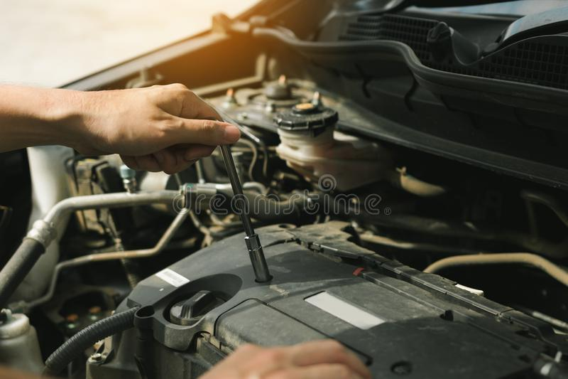 Sluit omhoog van hand professionele werktuigkundige die een auto in autoreparatiewerkplaats herstellen royalty-vrije stock foto's