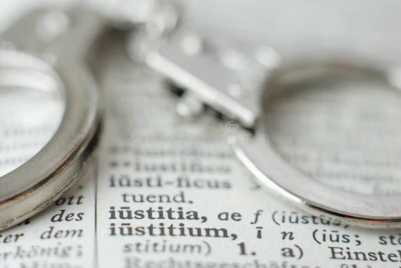Sluit omhoog van handcuffs op woordenboek royalty-vrije stock foto