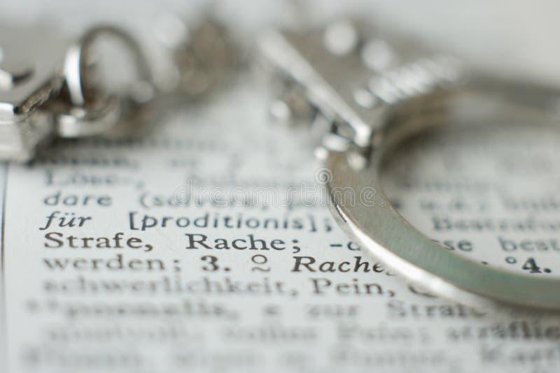 Sluit omhoog van handcuffs op woordenboek stock afbeelding