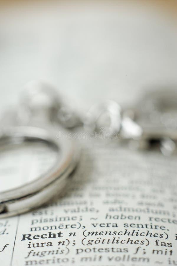 Sluit omhoog van handcuffs op woordenboek stock afbeeldingen