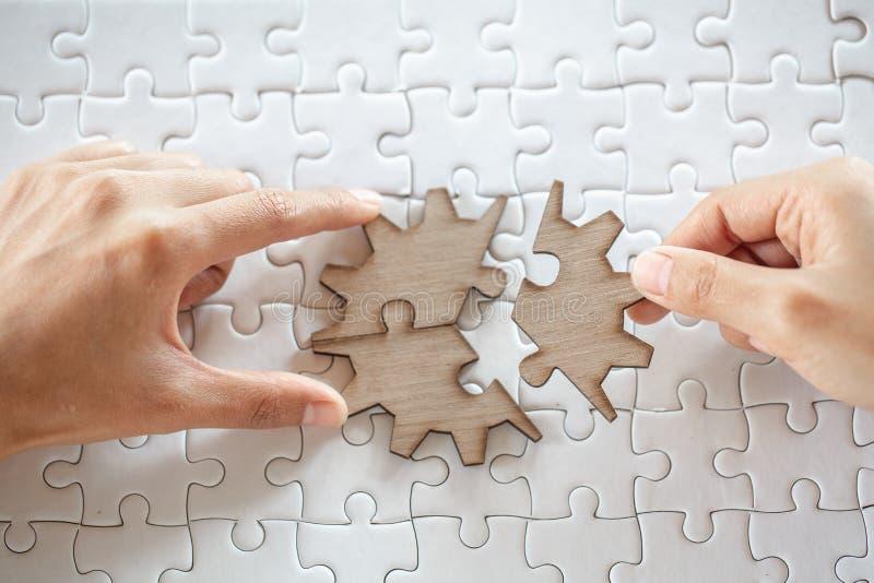 Sluit omhoog van handen bedrijfsvrouwen die figuurzaag puzzleon, het succes van de Groepswerkwerkplaats en strategieconcept aansl stock afbeeldingen