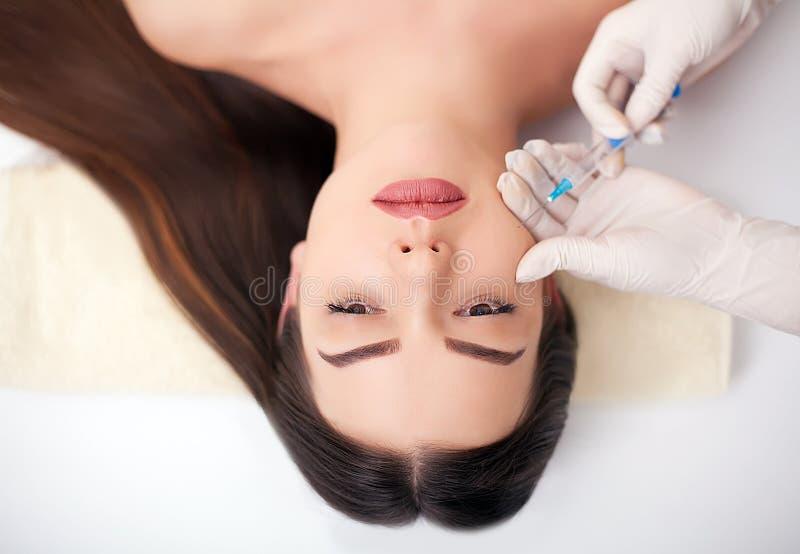 Sluit omhoog van handen van cosmetologist die botox injectie in vrouwelijke lippen maakt Zij houdt spuit De jonge mooie vrouw is  stock foto's