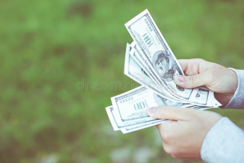 Sluit omhoog van handen die de honderd-dollar van de V.S. rekeningen op achtergrondgras tellen stock afbeeldingen