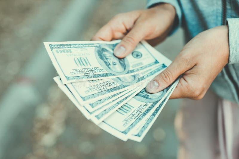Sluit omhoog van handen die de honderd-dollar van de V.S. rekeningen op de straat tellen stock fotografie